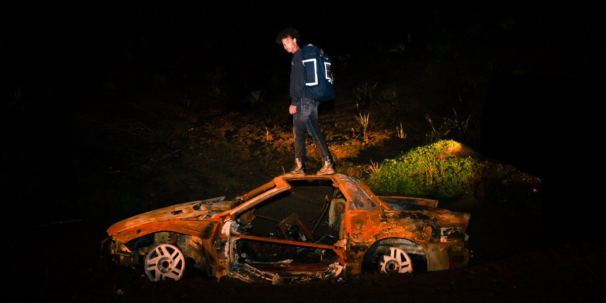 Model on top of abandoned car with backpack